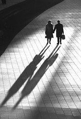 IMG_6487 (...like a chimp with coconuts) Tags: travel shadow people bw sun lines silhouette munich airport floor strangers silouette tiles figures stalking sniping longshadow