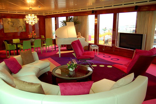 White baby grand piano in a multi coloured lounge dining space with bright bright bright red and magenta rug
