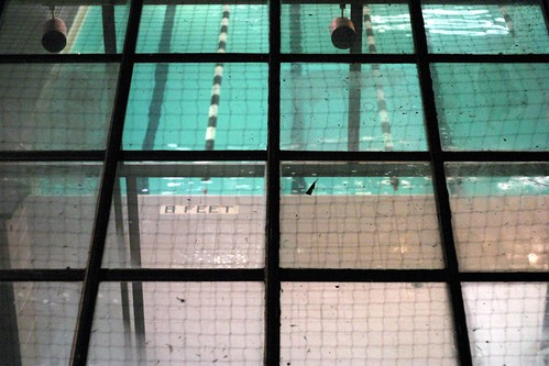 "photo of a swimming pool taken through the windows above, looking down on the water and ""8ft"" marker on the side"