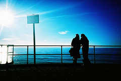 young lovers (john & yvonne) (lomokev) Tags: blue sea sky sun silhouette john lomo lca xpro lomography crossprocessed xprocess brighton yvonne lomolca agfa jessops100asaslidefilm agfaprecisa lomograph agfaprecisa100 cruzando precisa deletetag jessopsslidefilm file:name=lomo0106a03 johnsc flickr:user=yvoluna flickr:nsid=13520439n07