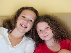 Cousins on a Couch (Monkey Mash Button) Tags: portrait girl smile digital pen hair lens ed four faces braces cousins picture pic olympus m teen curly together micro f18 zuiko 45mm thirds m43 mft mirrorless epm2