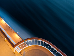 Deck Below (ralfrings) Tags: abstract blue brown deck gray guardrail illuminated light lights longexposure orange railing reflection sea shippingcontainer steel water white wood