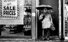 Shocked at the prices. (Mister G.C.) Tags: blackandwhite bw image streetshot streetphotography candid people photograph monthlychallenge monochrome urban town city woman lady eyecontact shocked expression umbrella doorway raining rainy shopwindows zonefocus zonefocusing snapfocus ricoh ricohgr pointshoot mistergc schwarzweiss strassenfotografie motherwell scotland britain greatbritain gb british uk unitedkingdom europe