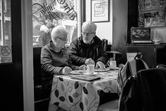 Together (Howie Mudge LRPS BPE1*) Tags: man woman elderly pensioner couple husband wife cafe café restaurant food drink tea coffee table chair window door sit sitting beard glasses people candid casual photography sign tablecloth barmouth gwynedd wales cymru uk blackandwhite blackwhite bw mono monochrome monochromatic fuji fujifilm fujixt1 fujifilmxt1 xf27mmf28 inside indoors