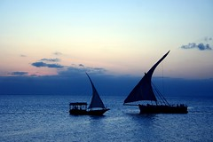 fins (Farl) Tags: africa blue sunset sea orange industry colors yellow backlight tanzania boats golden boat sailing sundown muslim horizon culture arab sail zanzibar tradition magical channel fins dhow phototip