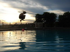 Flying boy (marlenells) Tags: sunset sky water freeassociation silhouette topc25 topv111 backlight clouds 1025fav fly flying fantastic jump topv555 topv333 perfect lovely1 gorgeous awesome 100v10f swimmingpool scoreme43 i500 123f20 bfv20