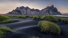 Dusk and Dawn (Franziska Liehl) Tags: iceland mountain dusk dawn sunrise sunset midnightsun summer icelandic vestrahorn stokksnes colorful sombre quiet peaceful landscape nature peak peaks sand dunes black blacksand grass volcanic evening night ocean water lowtide