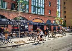 Foggy Dew_1534 (Stephen Wilcox - Jetwashphotos.com) Tags: road street travel people irish toronto building tree brick girl bike bicycle female bar hair table restaurant pub flickr chairs transport longhair bikes pedestrian patio sidewalk tables wp kingstreet irishpub foggydew kingst