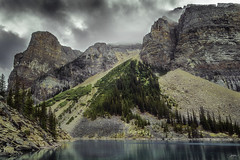 DSC_2455a-HDR-EditFAA (john.cote58) Tags: mountains water rocks boulder moss lakemoraine landscape outdoors outside nature alberta canada lakelouise icefieldsparkway lake pine trees design decoration art photography blue cliffwall postcard clouds overcast