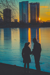 Colours in Winter: A Couple taking in The Sunset at Grenadier Pond (A Great Capture) Tags: ig agreatcapture agc wwwagreatcapturecom adjm ash2276 ashleylduffus ald mobilejay jamesmitchell toronto on ontario canada canadian photographer northamerica torontoexplore shadow winter l'hiver 2016 cold snow weather lights light sun sunny sunshine eos digital dslr urbannature scenery scenic sky himmel clouds nuvole wolken reflection outdoor outdoors vibrant colorful cheerful vivid bright ice frozen sunset atardecer tree streetphotography streetscape street silhouette people person social view viewing look looking blue orange red gold golden shore pond wow walking couple