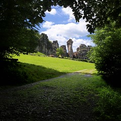 Externsteine juts up from the surrounding German forest (Bn) Tags: summer lake rock stone forest germany walking high topf50 tales hiking earth walk hike holes holy route sacred cult mysterious land limestone priest pillars prehistoric wald topf100 paganism crusader surrounding sanctuary imposing important enormous germanic teutoburgerwald externsteine drilled symbolize 100faves 50faves teutoburg 38m externsteinerstr 32805hornbadmeinberggermany thegreatpillar stonesoftheegge