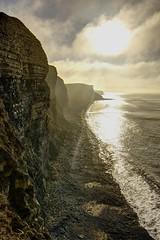 Deciding to run (pauldunn52) Tags: cliffs glamorgan heritage coast wales sunlight cloud sea shimmering pebble beach
