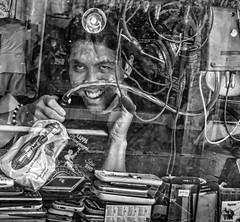 Mad Scientist (FotoGrazio) Tags: repair asian portrait composition unorganized congestion vendor reflection fotograzio clutter photographicart internationalphotographer messy mad worldphotographer busy male contrast throughawindow wetmarket waynegrazio travelphotography streetphotography forsale mobilephones man artofphotography business lifeinthephilippines internationalphotographers portraiture pinoy streetportrait market smile waynesgrazio streetscene pacificislanders people repairshop sandiegophotographer californiaphotographer digitalphotography philippines documentaryphotography cellphone laugh madscientist flickr 500px photographicartist wires photography cases eyes filipino scientist spareparts brokenphones blackandwhite evillaugh socialdocumentary