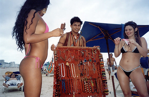 Two girls in string bikini buying bangles from a bangles seller on Ipanema Beach