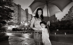 dusk, rain, and affection (ioannis lelakis) Tags: street city family urban bw 20d love girl rain sepia night umbrella canon children asian hug asia cityscape affection dusk south july 2006 korea safety muse muses safe care 12th residential protection wonju