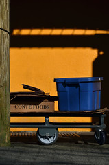 Late afternoon outside the market (James_D_Images) Tags: publicmarket cart box orange wall blue plastic tote frontlit light shadow utility pole brick sidewalk granvilleisland
