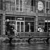 High & dry (John Riper) Tags: johnriper street photography straatfotografie square vierkant bw black white zwartwit mono monochrome netherlands candid john riper canon 6d 24105 l hoogstraat markthal jamie oliver albert heijn wet pavement rain dark bench girl young woman sitting smart phone people pigeon italian