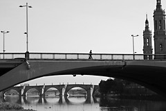 Walking on bridges (Daniel Nebreda Lucea) Tags: city ciudad walk walking andado andar travel viajar black white blanco negro light luz bridges puentes architecture arquitectura urban urbano monochrome monocromatico water agua river rio building edificio construccion structure estructura people gente man hombre sky cielo canon 50mm 60d aragon spain españa europe europa old viejo antiguo modern moderno perspective perspectiva composition composicion lines lineas