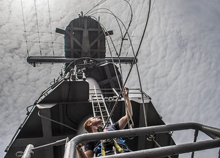 A Sailor lowers lines on the aft mast of USS Essex.