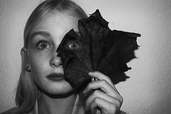 Looking through a leaf (mollygreen2016) Tags: black white bw blackandwhite photography portrait girl leaf closeup headshot dark light night winter whitebackground background indoors art national people newyear 2017 christmas family old new house niece auntie love