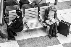 Defiance (DobingDesign) Tags: people blackandwhite london reading sitting looking chairs squares sandals interior citylife indoor anger luggage pointofview trainstation thinking angry mobilephone inside suitcase handbag straps liverpoolstreetstation poised humans commuters lookingaway offset defiance sulking clutching crosswordpuzzle huddled warching stationfurniture humanoflondon