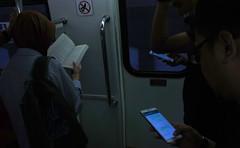 Reading - Kuala Lumpur (Chot Touch) Tags: ricohgxr kualalumpur train monorail ktm malaysia book handphone lowlight