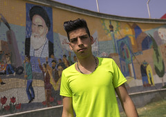 Young Man With Western Haircut In Front Of Ayatollah Khomeini Poster, Shemiranat County, Tehran, Iran (Eric Lafforgue) Tags: street portrait people haircut signs colour men fashion sign horizontal painting hair advertising poster dead outdoors photography death mural memorial asia peace adult iran propaganda painted muslim islam hipster persia icon national hero posters illegal males billboards leader iranian tehran hairstyle rule adultsonly heroic oneperson outlaw teheran imam fluo ayatollah sharia theran commemorate colorimage khomeini lookingatcamera  onemanonly  colourimage  iro gelledhair  religiouspolice fashionnable  shemiranatcounty iran150808