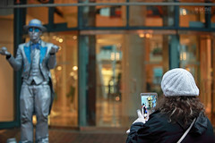 Subject Is In The Lens Of The Shooter (Ian Sane) Tags: ian sane images subjectisinthelensoftheshooter photographer streetperformer busker bokeh candid street photography downtown portland oregon wellsoviatt mrstatue silverman pioneer place southwest 5th avenue morrison canon eos 5d mark ii two camera ef70200mm f28l is usm lens
