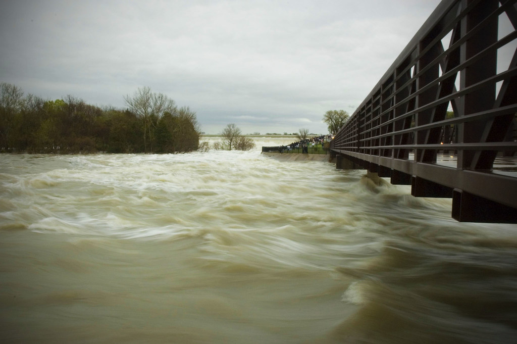 This was from the big flood in March 2006.  This image is taken from the base of the ped bridge at the spillway.  It basically ate away the entire flood wall where the people are standing.  To this day they are working on repairing and reinforcing that area.