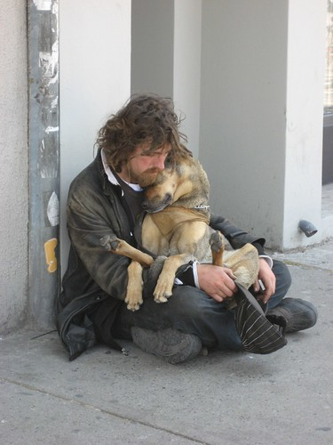 Homeless man cuddles dog