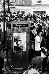 Poster Boy (JacobSmithFilm) Tags: street uk carnival boy party portrait england people music white black london history film festival contrast canon poster photography 50mm high exposure phone box jacob 14 crowd arches smith gritty save celebration and caribbean splash multicultural reggae dub brixton britian equality 600d jacobsmithfilm