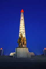 Pyongyang at the blue hour. Juche Tower & bronze sculpture of worker, intellectual & peasant