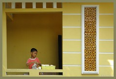 Boy folding napkins / Hue,  Vietnam (swampzoid) Tags: boy window yellow child vietnam passage hue