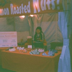 Roasted Nuts (Anne Abscission) Tags: sausagefest everettsausagefest everett washington sausagefestival carnival fair dusk vendor foodvendor roastednuts nuts people person woman kodakinstamatic814 kodakinstamatic kodakgold 200asa kodakgold200 126film 126instamatic expiredfilm expired filmphotography analog filmisnotdead ishootfilm vintagecamera rangefinder tent outdoor