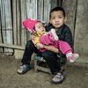 HOLDING SISTER - HOLDING HANDS, LAOS. Visit to a Hmok village near Luang Prabang.  A touching moment beyond the edge of everyday tourism, but most welcoming and anxious to sell their crafts.  P1181134 (Marc Weinberg) Tags: hands holdinghands sister brother holdingsister childcare child children laos hmok laungprabang tender tendermoment touchingmoment touching caring travel travelagent adventuretravel photjournalism photojournalist freelance getolympus portrait