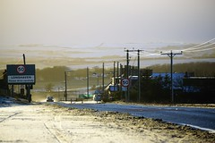 Longhaven in winter. (artanglerPD) Tags: longhaven village 50 miles per hour winter sunshine wires lights poles road snow car spray