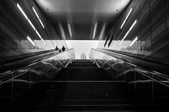 the last descent / the man who escalated to earth (Özgür Gürgey) Tags: 2017 20mm bw d750 hamburg nikon voigtländer architecture escalator reflection shadow silhouette stairs station subway überseequartier germany symmetry