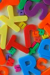 a jumble of alphabet magnets in two different sizes