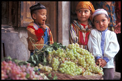XINJIANG - CHINA (BoazImages) Tags: china travel people cute frutas smile topv111 fruit kids colorful asia muslim islam hats forsakenpeople grapes xinjiang silkroad centralasia vegetales mercados fruitstall