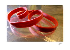 Rubber Band 2 (jesse1dog) Tags: rubber band rubberband red reflection twisted tabletop abstract golden