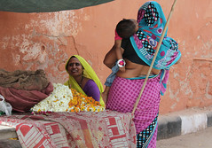 Jaipur Ladies (cowyeow) Tags: street city travel red people woman baby india color wall composition child candid fat indian mother jaipur rajasthan flowerseller indianwoman