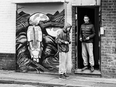 Northern Quarter #159 (Peter.Bartlett) Tags: manchester niksilverefex art unitedkingdom people facade doorway monochrome urbanarte streetphotography olympuspenf lunaphoto man urban peterbartlett candid uk m43 microfourthirds noiretblanc bw eyecontact wall blackandwhite city men