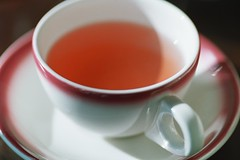 pink tea in pink-rimmed teacup - by cafemama