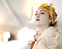 Sakura Festival: Out of the Light (Ryan Brenizer) Tags: nyc newyorkcity red woman white newyork topf25 brooklyn japanese nikon performance 2006 noflash depthoffield april highkey d200 unposed brooklynbotanicalgardens sakurafestival 70200mmf28gvr cherryblossomfesival nikonstunninggallery