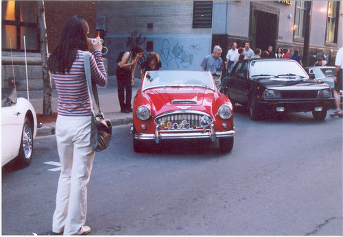 A girl photographing an Austin-Healey car, Montreal. by Steve Brandon