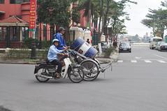Helping hand (Roving I) Tags: motorcycles helping riders cyclos loads pushing oilbarrels streets danang vietnam