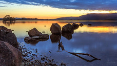 Sunset over Milarrovhy Bay (Landscape) (MilesGrayPhotography (AnimalsBeforeHumans)) Tags: britain bay milarrochybay canon 6d canon6d 1635 ef1635mmf4lisusm calm dusk eos ef europe evening f4l glow landscape longexposure lens loch le lochlomond milarrochy nd nd1000 10stopper outdoors photography tranquil reflections rocks scotland sky scenic sunset twilight uk unitedkingdom waterscape winter