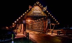 Holz Brucke (Wes Iversen) Tags: clichesaturday frankenmuth hcs holzbrucke michigan nikkor18300mm bridges coveredbridges flags landmarks lights night touristattractions wood woodenbridges