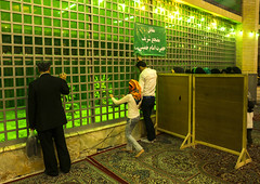 Pilgrims Praying In Front Of The Tomb Of Ayatollah Ruhollah Musawi Khomeini Buried Next To His Son Ahmed Khomeini, Shemiranat County, Behesht-e Zahra, Iran (Eric Lafforgue) Tags: travel green grave photography death persian memorial shrine asia respect iran symbol buried muslim islam faith religion tomb persia visit indoors mausoleum devotion burial leader iranian spirituality fullframe tehran orient revolutionary cultures pilgrimage tombs pilgrim attraction pilgrims koran offerings shiite placeofworship mausoleums qom ghom famousplace khomeini   beheshtezahra colourimage qum  iro ayatollahkhomeini shiiteislam iranianculture  placeconcerningdeath  shemiranatcounty iran150900