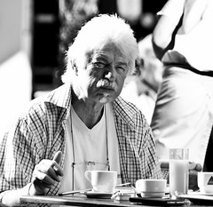 Continental breakfast. (Neil. Moralee) Tags: man old mature portrait portraite face bright white hair sunshine breakfast eat eating street candid wrinkles creases lines cup glass black mono monochrome bw blackandwhite cafe coffee funchal madeira neil moralee nikon d7100 18300mm zoom goatee beard facial shirt vest table